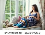 Young Pregnant Woman Sitting O...