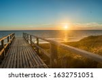 beautiful view onto the North Sea from a boardwalk on sylt taken at sunset with dunes in the foreground, the beach in the background and the warm light of the evening sun coloring the whole picture