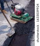 Small photo of Worker use vibratory plate compactor compacting asphalt at road repair