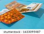 Small photo of Pills blister on money euro banknotes for pharmaceutical cost. Rising prices of healthcare system. Medical on blue background. Increased costs for coronavirus pandemic. Vaccine and antibiotic
