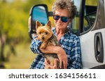 RV Road Trip with Dog Friend. Retired Woman with Her Pet on Vacation. Side to Camper Van Motorhome. Australian Silky Terrier.  - stock photo