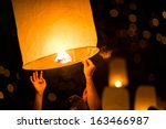 people is launching sky lantern ... | Shutterstock . vector #163466987