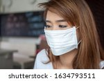 woman wearing face mask from having flu infection; concept of Wuhan virus, corona virus, H5N1, H1N1, bird flu, pig flu, avian influenza, swine influenza, pneumonia, lung inflammation, epidemic fever