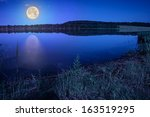 Mountain lake and forest on the embankment at night - stock photo