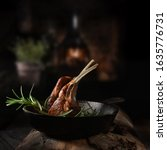Small photo of Traditional, roasted rack of lamb cutlets in a wrought iron skillet with rosemary herbs shot against a dark, rustic background with generous accommodation for copy space.