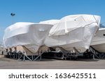Small photo of power boat parked covered white protective plastic film New boats in cover casing shrink wrap on sailboat stored for winter