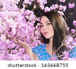 woman in the flowers of... | Shutterstock . vector #163668755