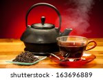 Stock photo a cup of black tea with teapot in the background 163696889