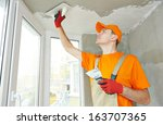 Small photo of Plasterer at indoor ceiling renovation decoration with float and plaster
