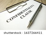 Small photo of Confidentiality clause with pen on desk, business concept