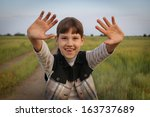 young girl standing on a field... | Shutterstock . vector #163737689