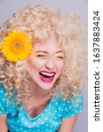 Small photo of Beautiful blonde girl with voluminous curly hairstyle, in a blue polka dot blouse and with a flower of a sunflower in her hair on a gray background, laughs joyfully