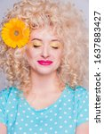 Small photo of Beautiful blonde girl with voluminous curly hairstyle, in a blue polka dot blouse and with a flower of a sunflower in her hair on a gray background