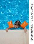 Small photo of aerial shot: four years old blonde child with orange floater sleeves in arms, armbands, clinging or holding on to the curb of the swimming pool, with blue transparent water