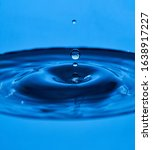 Water drop splash blue colored. ...