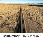 Small photo of Train tracks run straight ahead for as far as the eye can see through a sandy desert landscape. Miles long straightaway.