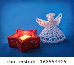 Candlestick star and knitted Christmas angel on a blue background. first Advent - stock photo