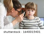 Regular pediatric medical examination at doctor. Female ENT wears glasses and jewelry, she examines ear small patient with special device. Girl sits quietly on couch and awaits end procedure. - stock photo