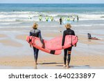 Two Young Male Surfers Walking...