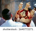 Small photo of Jewish man in black kippah carrying a Torah scroll in a beautifully ornate red case with golden bells and crowns (rimmonim) and other decorations - Simchat Torah; Western/Wailing Wall, Jerusalem