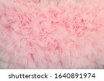 Small photo of Textured background of ruffled wavy fabric pastel colour- pink