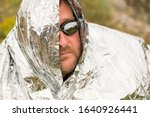 Small photo of the bearded man has foil on his head and swimming glasses on his eyes. strange man on the background of the sky it is unclear why so dressed