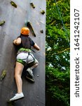 Small photo of Woman in shorts and black shirt with safety equipment climbing an artifical climbing wall.