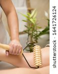 Small photo of Closeup of the maderotherapy anti-cellulite leg massage with wooden roller massager