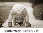One-year baby girl playing upside down on the street - stock photo