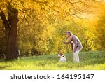 Stock photo senior woman walking her beagle dog in countryside 164195147