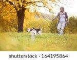 Stock photo senior woman walking her beagle dog in countryside 164195864