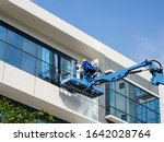 SINGAPORE – 26 DEC 2019 – Low angle shot of construction workers in a metal basket painting and cleaning the exterior of an industrial building - stock photo