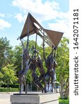 Small photo of Lausanne, Switzerland - July 13, 2019: The Elan (L'Elan). Bronze sculpture of the Olympic flag, carried aloft by five stylized athletes. Nag Arnoldi