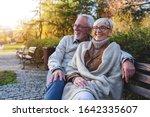 Smiling Senior Couple Sitting...