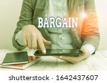 Small photo of Writing note showing Bargain. Business photo showcasing Negotiate terms and conditions of transaction ask for discount Business concept with communication mobile phone.