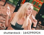 Small photo of Hungry young sports woman eating protein bars while standing on sports ground. Beautiful greedy blonde fitness girl posing and enjoying healthy muesli and cereal snacks outdoors. Nutrition for sport