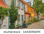 A traditional Scandinavian Cargo bicycle (Christiania Bike) parked at a house entrance in a cozy downtown street by a colorful facade. Danish lifestyle and culture illustration - Aarhus, Denmark