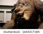 Small photo of Anaheim, California - April 16 2015: A life size rancor creature statue at Star Wars Celebration 2015.