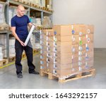Small photo of Man wrapping (stretching) of a loaded pallet with foil - most common and fastest way to stabilize the goods on the pallet. Worker (warehouseman) is using manual stretch foil to protect the products.