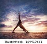 Man Doing Yoga On The Beach...