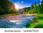 river near  forest at the foot of mountain  - stock photo