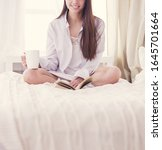 Woman Sitting In Bed Reading A...