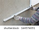worker placing aluminum batten... | Shutterstock . vector #164576051