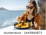 Woman eating paella ...