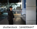 Small photo of Security Guard Walking Building Perimeter With Flashlight At Night