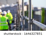 Small photo of Architect on site Silhouette Construction workers on a scaffold. Extensive scaffolding providing platforms for work in progress. Men walking on roof surrounded by scaffold - Focus on scaffolding frame
