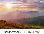 mountain landscape. valley with stones on the hillside. forest on the mountain under the beam of light falls on a clearing at the top of the hill. in morning light - stock photo