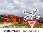 """Sign """"Raiway Crossing"""" and sign """"Give Way"""" in front of the Railway Bridge over the Taramakau River at Camerons, West Coast, New Zealand."""