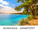 Zlatni Rat beach, Golden Horn or Golden Cape in Bol town, Brac Island, Croatia. Gravel beach, pine trees, boats and turquoise water of Adriatic Sea on sunny summer day. Famous tourist destination - stock photo