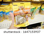 Small photo of Long Beach, California/United States - 02/12/2020: A hand holds a package of Good Sense shelled pumpkin seeds, on display at a local grocery store.